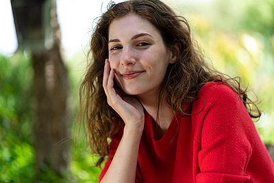 Smiling woman with hand on chin in garden - p300m2286833 by Steve Brookland
