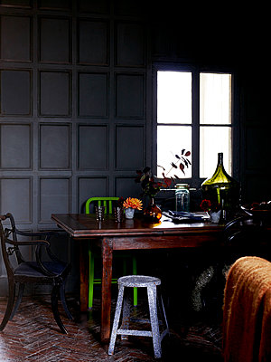 Backlit objects on wooden table in panelled room - p349m2167827 by Polly Wreford
