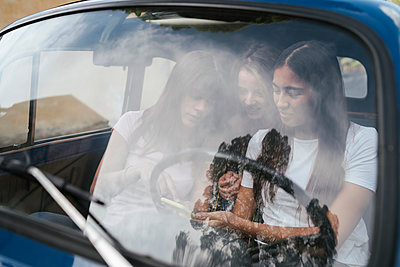 Friends using smartphone inside car - p429m2097348 by Lorenzo Antonucci