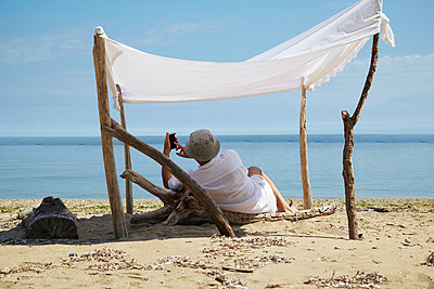 Woman relaxing under homemade shade on beach - p555m1415408 by Rolf Bruderer