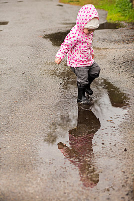 Caucasian girl wearing boots splashing in puddle - p555m1482035 by Adam Hester