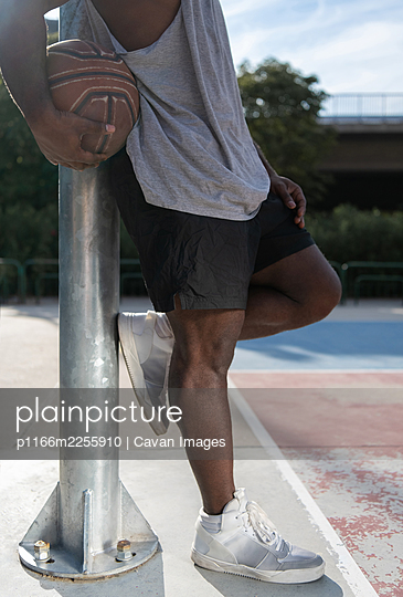 Cropped ethnic athlete resting on basketball court - p1166m2255910 by Cavan Images