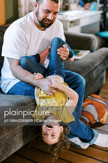 A father and his daughter playing together in the living room - p1166m2269699 by Cavan Images