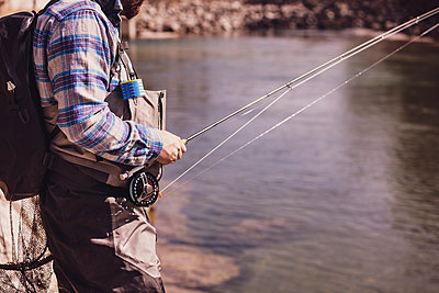Fly fisherman catching fish from river on sunny day - p300m2220700 by Studio 27