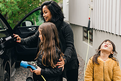 Woman teaching daughter to charge electric car at charging station - p426m2194960 by Maskot