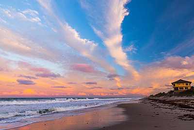 Sunset over a beach and yellow house on the Atlantic coast; Satellite Beach, Florida, United States of America  - p442m1520056 by Steven Miley