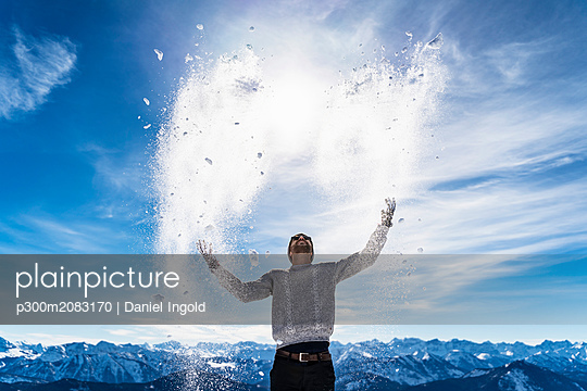 Germany, Bavaria, Brauneck, man in winter playing with snow in the mountains - p300m2083170 by Daniel Ingold