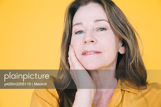 Portrait of senior woman against yellow background - p426m2205119 by Maskot