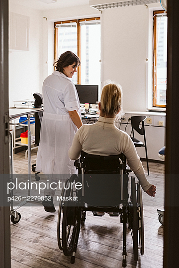 Smiling female medical expert looking at disabled woman visiting at medical clinic - p426m2279852 by Maskot