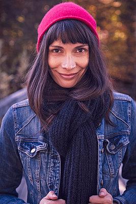Portrait of smiling woman wearing red woolly hat and denim jacket - p300m2159952 von Studio 27