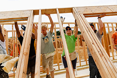Volunteers lifting framed wall at construction site - p555m1522826 by Roberto Westbrook
