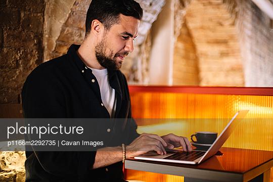 Happy businessman using laptop computer at cafe - p1166m2292735 by Cavan Images