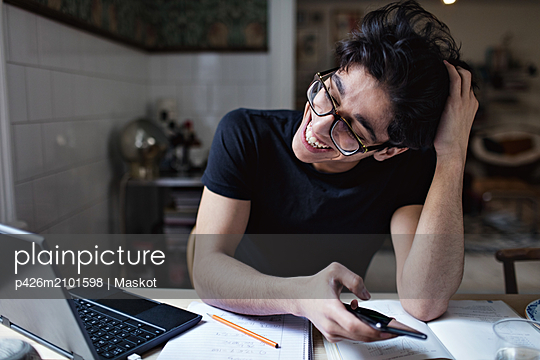 Cheerful social media addicted young man using mobile phone while doing homework - p426m2101598 by Maskot