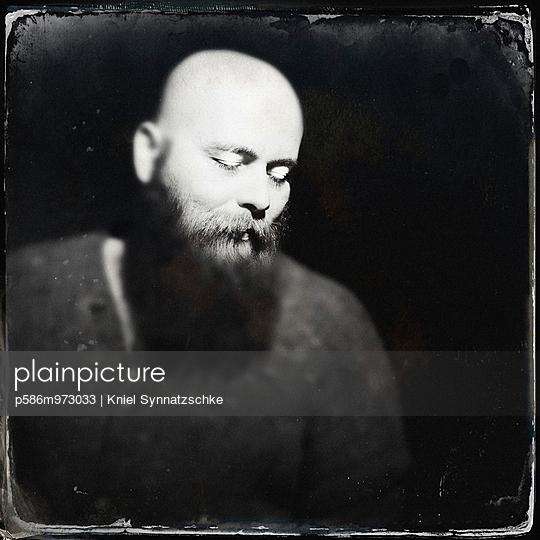 Mann mit Glatze, Vollbart und geschlossenen Augen - p586m973033 von Kniel Synnatzschke