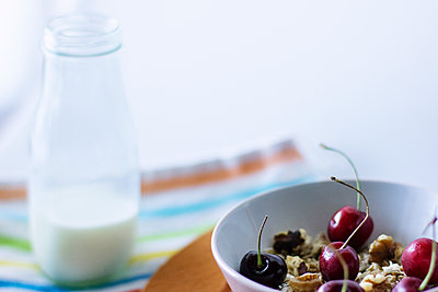 Walnuts and cherries in bowl by milk bottle on table - p1166m1151176 by Cavan Images