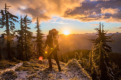 Rear view of backpacker hiking with a scenic mountain view. - p1166m2255894 by Cavan Images