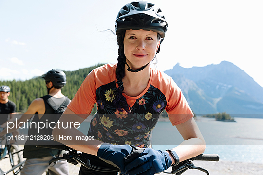 Portrait confident woman mountain biking at sunny lakeside - p1192m2129206 by Hero Images