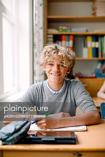 Smiling blond teenage boy at desk in classroom - p426m2298657 by Maskot
