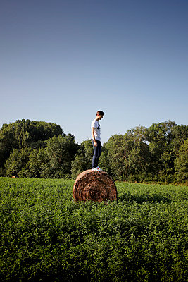 Young man on a hay bale - p1105m2288361 by Virginie Plauchut