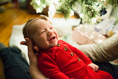Smiling baby girl looks up at mother during Christmas celebration - p1166m2095643 by Cavan Images