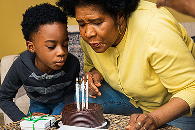 Grandmother and grandson blowing candles on birthday cake at home - p1166m2279401 by Cavan Images