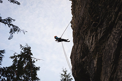 Low angle view of rock climber climbing the rocky cliff - p1315m1565253 by Wavebreak