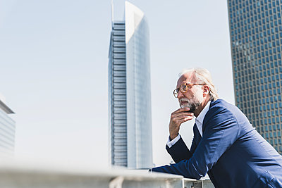 Serious mature businessman in the city looking around - p300m1587395 by Uwe Umstätter
