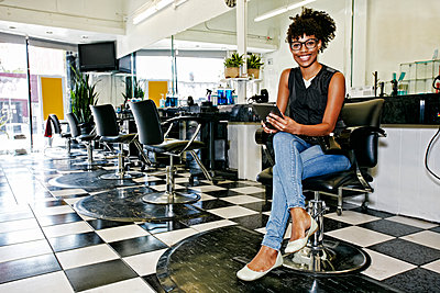 Mixed race hairstylist smiling in salon - p555m1410461 by Peathegee Inc