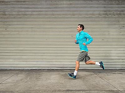 Caucasian man running on city street - p555m1420161 by Erik Isakson