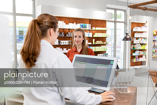 Female pharmacist using computer while customer standing at checkout in store - p300m2251794 by Florian Küttler