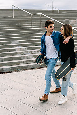 Young couple with skateboards walking near steps - p300m2256830 by Xavier Lorenzo