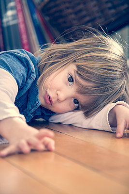Portrait of little girl lying on the floor - p300m911345f by Larissa Veronesi