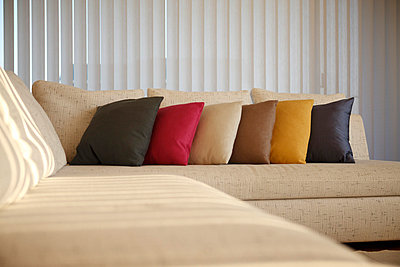 Multicolored Cushion In A Row On Sofa  - p307m700485f by Imaggio