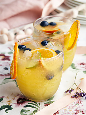 Cocktails with orange slices, berries and ice cubes - p429m2019676 by Debby Lewis-Harrison
