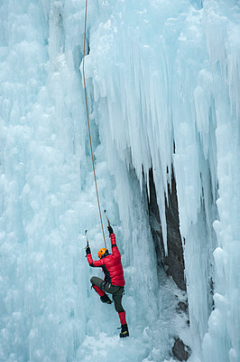 Caucasian man climbing ice wall - p555m1479338 by Pete Saloutos
