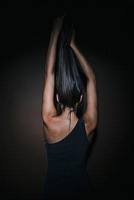 Junge Frau mit langen dunklen Haaren posiert, Rückansicht - p586m953777 von Kniel Synnatzschke