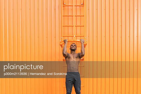 Athlete doing chin-ups in front of an orange wall - p300m2113936 von Hernandez and Sorokina