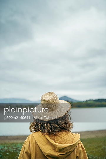 Rear view of young woman wearing straw hat, looking to a lake - p300m2140641 by Mikel Taboada
