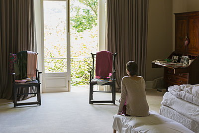Woman looking out balcony window in luxury home showcase bedroom - p1023m1173591 by Astronaut Images