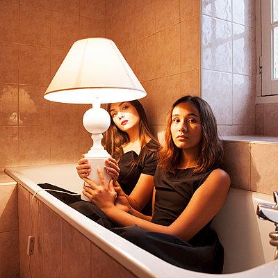 Zwei Frauen mit Lampe in der Badewanne - p1105m2133107 von Virginie Plauchut