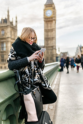UK, London, young woman using her smartphone on Westminster Bridge - p300m1188556 by Marco Govel