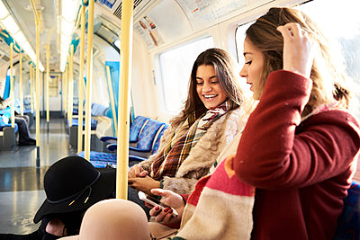 UK, London, two happy women in underground train using cell phone - p300m2103813 by Ivan Gener