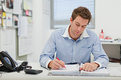 Businessman working at desk - p429m659551f by Hybrid Images