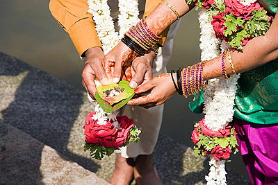 Couple holding puja in indian wedding ceremony - p9246581f by Image Source