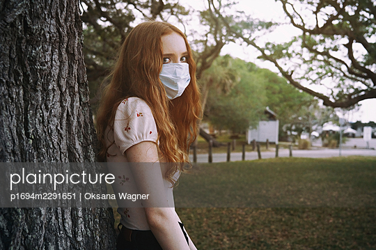 Young red-haired woman wearing protective face mask and looking a camera in empty public park - p1694m2291651 by Oksana Wagner