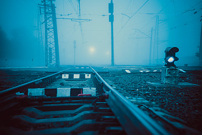 Surface level shot of railroad tracks during foggy weather - p1166m2025036 by Cavan Social