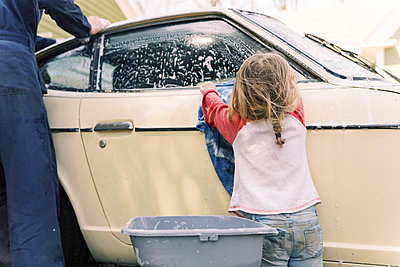 A father and his toddler daughter washing a classic car together. - p1166m2190658 by Cavan Images