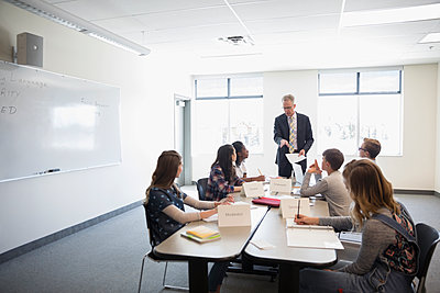 Teacher and middle school students in debate club classroom - p1192m1473292 by Hero Images