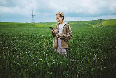 Smiling woman holding phone in field in Crimea, Ukraine - p1427m2163662 by Oleksii Karamanov