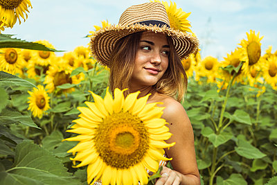 Young woman with a straw hat smiling in a field of sunflowers - p300m2028680 by Aitor Carrera Porté